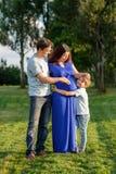 Famille enceinte heureuse du nouveau bébé trois de attente Photographie stock