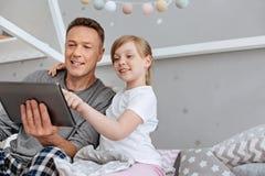 Famille engagée mignonne observant quelque chose sur le comprimé Photo stock