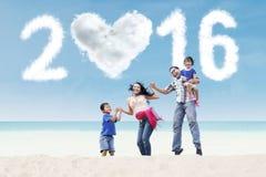 Famille espiègle sur la plage avec les numéros 2016 Photographie stock libre de droits