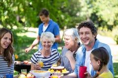 Famille et amis ayant un pique-nique avec le barbecue Photographie stock