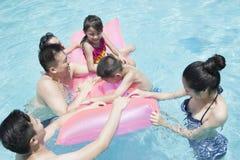 Famille et amis jouant dans l'eau à la piscine Image stock