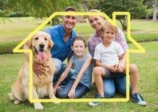 Famille et chien se reposant en parc contre le contour de maison à l'arrière-plan Images stock