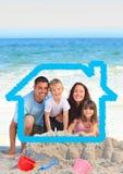 Famille et chien sur la plage contre le contour à la maison à l'arrière-plan photographie stock