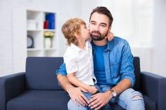 Famille et concept d'amour - petit fils embrassant son père Image stock