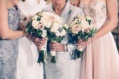 Famille et jeune mariée de génération de femmes tenant des groupes de fleurs le jour du mariage Photographie stock libre de droits