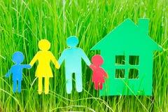 Famille et maison de papier dans l'herbe images libres de droits