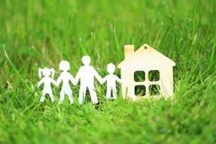 Famille et modèle de maison au-dessus d'herbe verte Image libre de droits