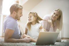 Famille et ordinateur portatif Jour pour l'amusement images libres de droits