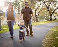 Famille ethnique heureuse de chemin mélangé marchant en stationnement Photographie stock