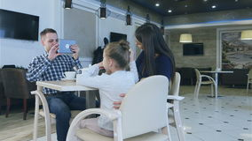 Famille européenne amicale prenant la photo en café pendant leur dîner clips vidéos