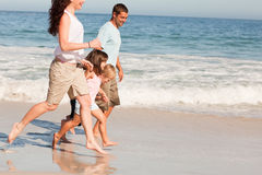 Famille exécutant sur la plage image libre de droits