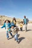 Famille exécutant sur la plage de l'hiver Photographie stock