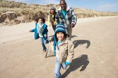 Famille exécutant sur la plage de l'hiver Photo stock