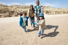 Famille exécutant sur la plage de l'hiver Photos stock