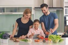 Famille faisant cuire la préparation alimentaire de repas ensemble d'intérieur image libre de droits