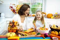 Famille faisant cuire la soupe à potiron pour le déjeuner de Halloween photo stock