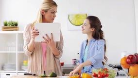 Famille faisant cuire le dîner utilisant le PC de comprimé à la cuisine banque de vidéos