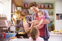 Famille faisant cuire le repas dans la cuisine ensemble Images libres de droits