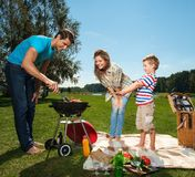 Famille faisant cuire sur un gril dehors Image stock