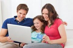 Famille faisant des emplettes en ligne à la maison Photos libres de droits