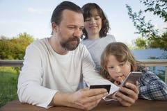 Famille faisant des emplettes en ligne par l'intermédiaire de la terrasse une soirée d'été Photos libres de droits