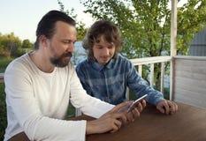Famille faisant des emplettes en ligne par l'intermédiaire de la terrasse une soirée d'été Images libres de droits