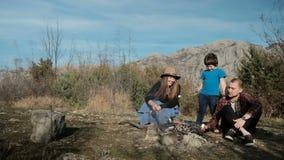 Famille faisant frire le feu en jeu de zéphyr ayant le pique-nique dehors en nature banque de vidéos