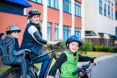 Famille faisant un cycle, mère avec le vélo heureux d'équitation d'enfant dehors Images libres de droits