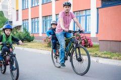 Famille faisant un cycle, père avec le vélo heureux d'équitation d'enfant dehors Image stock