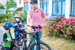 Famille faisant un cycle, père avec le vélo heureux d'équitation d'enfant dehors Photo libre de droits