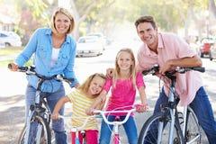 Famille faisant un cycle sur la rue suburbaine image stock