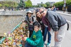 Famille fermant à clef le cadenas d'amour au pont de la Seine à Paris, France Photographie stock libre de droits