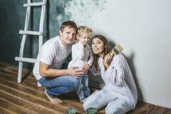 Famille, fille heureuse avec la maman et papa faisant la réparation à la maison, peinture Photo stock