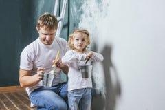 Famille, fille heureuse avec le papa faisant la réparation à la maison, murs de peinture, images libres de droits