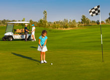 Famille folâtre jouant le golf sur un terrain de golf Photos libres de droits
