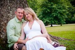 Famille : Futurs parents s'asseyant dehors par un arbre Image libre de droits