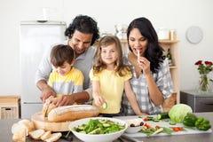 Famille gai préparant le déjeuner ensemble dans le kitch Image stock