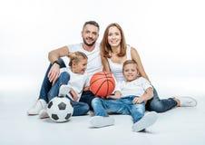 Famille gaie avec des boules du football et de basket-ball Photos stock