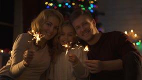 Famille gaie avec des lumières de Bengale regardant à la caméra, appréciant Noël magique banque de vidéos