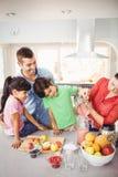 Famille gaie avec le jus de fruit de versement de mère dans la cruche Image stock