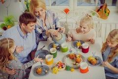 Famille gaie ayant l'amusement et appréciant le thé et les petits gâteaux aromatisés Photo stock