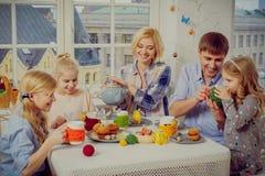 Famille gaie ayant l'amusement et appréciant le thé et les petits gâteaux aromatisés Image libre de droits