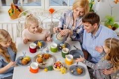 Famille gaie ayant l'amusement et appréciant le thé et les petits gâteaux aromatisés Images libres de droits
