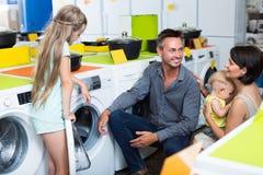 Famille gaie choisissant la machine à laver Images libres de droits