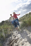 Famille gaie courant par des dunes de sable Photo stock