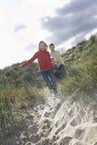 Famille gaie courant par des dunes de sable Images stock