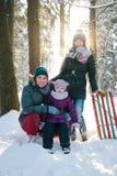 Famille gaie détendant dans la forêt d'hiver Photos libres de droits