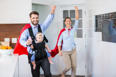 Famille gaie dans le costume de super héros avec le bébé Photographie stock libre de droits
