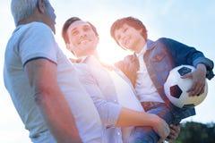 Famille gaie discutant le football après avoir joué dehors Photographie stock libre de droits