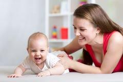 Famille gaie heureuse Mère et bébé jouant, riant et étreignant Image stock